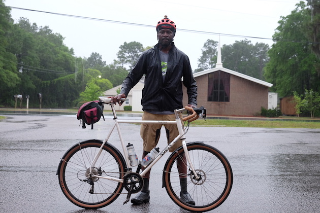 Cyclist standing in the rain behind a Surly Midnight Special bike, white, with a seat pack, right profile view