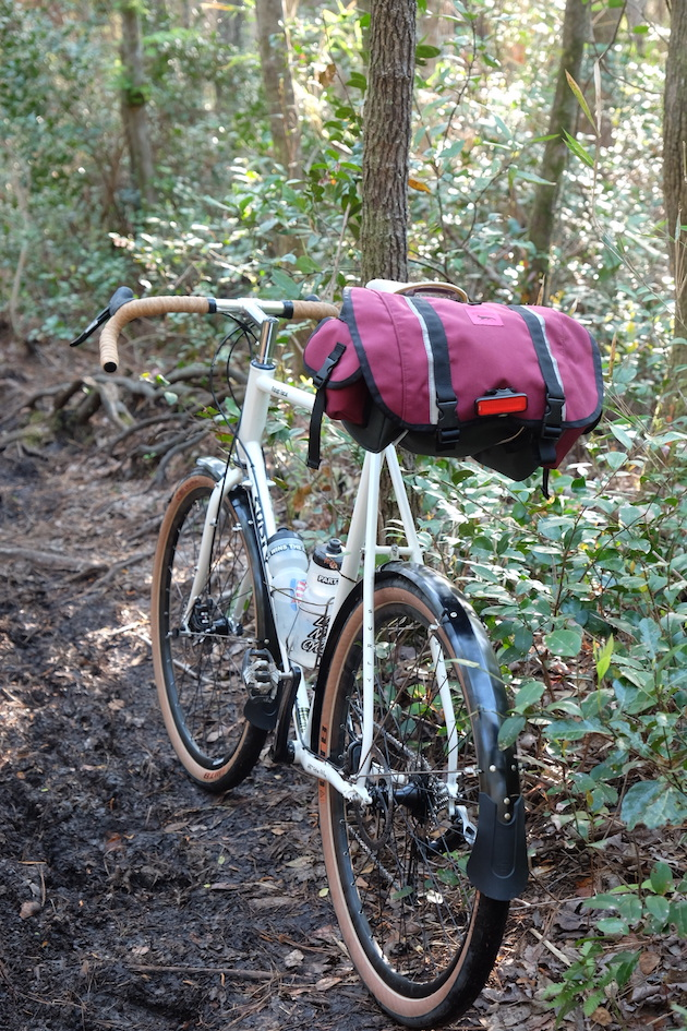 Surly Midnight Special bike, white, with red seat pack facing away down a dirt trail in the woods