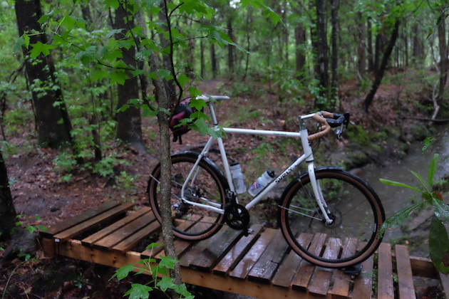 Right side view of a Surly Midnight Special bike, white, with seat pack, stand on a wet, wood double pallet in the trees