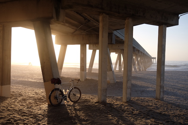 Surly Midnight Special bike leaning on a support in the sand under a pier with the sun shining through