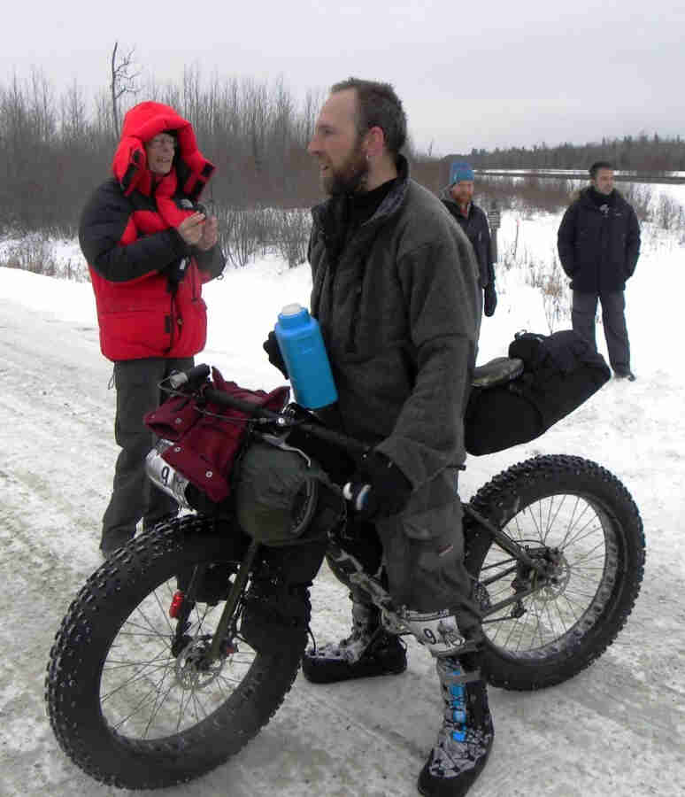 Left side view of a Surly Moonlander fat bike, loaded with gear and a cyclist standing over, on an icy gravel road