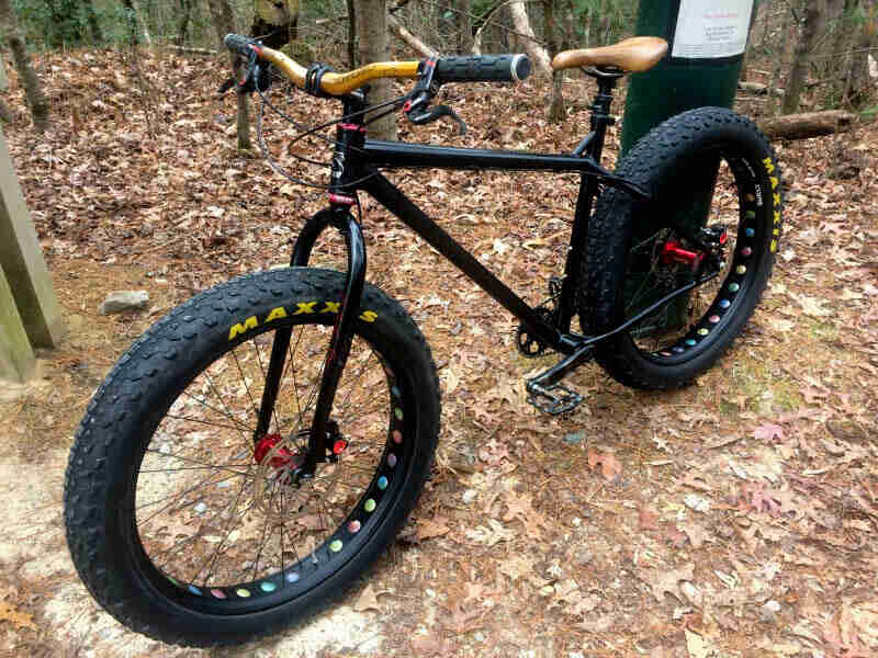 Front left view of a black Surly fat bike, standing on top of grass and leaves, with trees in the background