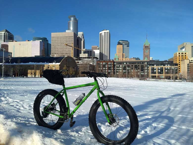 Surly Ice Cream Truck fat bike,green, with seat pack and water bottle in snowy field and buildings of Minneapolis behind