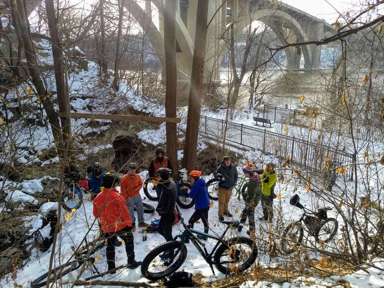 A group of cyclists and their bikes gather under a river bridge in the woods on a patch of snow