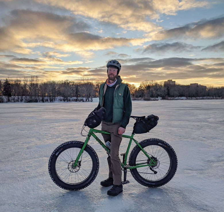 Cyclist stands on frozen lake with Surly Ice Cream Truck fat bike with seat bag, water bottle, and trees in the distance