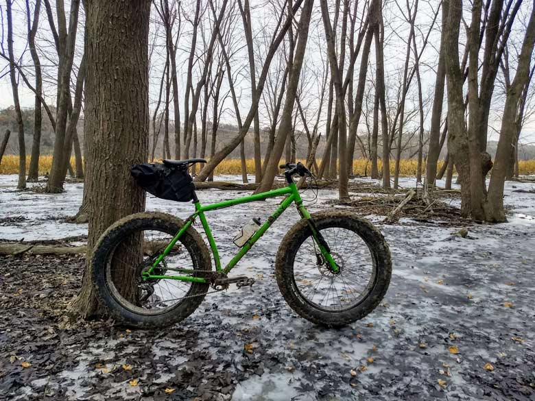 Surly Ice Cream Truck fat bike, green, with seat pack and water bottle leans against a tree in the woods on an icy patch