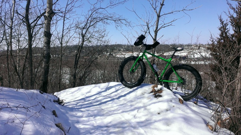 Left side view of a green Surly fat bike, parked on a snowbank on the side of a snow covered trail in the woods