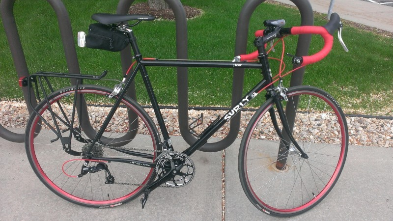 Right side view of a black Surly Pacer bike with red handlebar, leaning along a bike rack on a sidewalk
