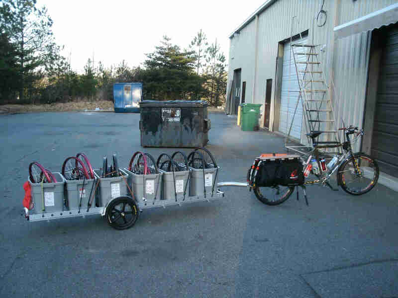 Right side view of a Surly Big Dummy bike with a trailer of bins, full of bike rims, on an outdoor warehouse lot