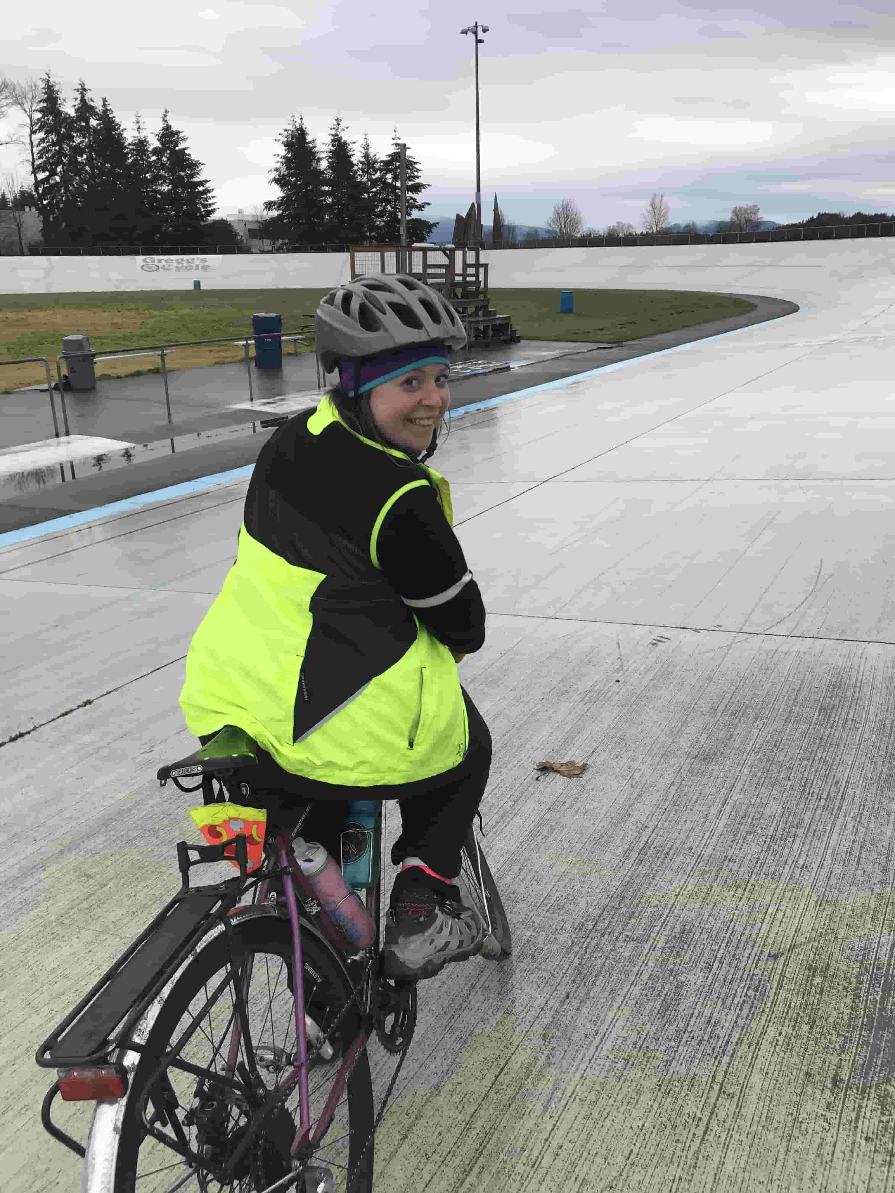 Cyclist looking back while seated on a bike in the middle of a race track wearing biking gear on a rainy day
