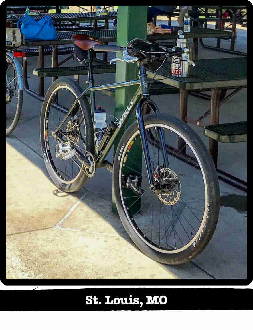 Front Left view of a Surly Karate Monkey bike, leaning on a post, under a park gazebo - St. Louis, MO tag below image