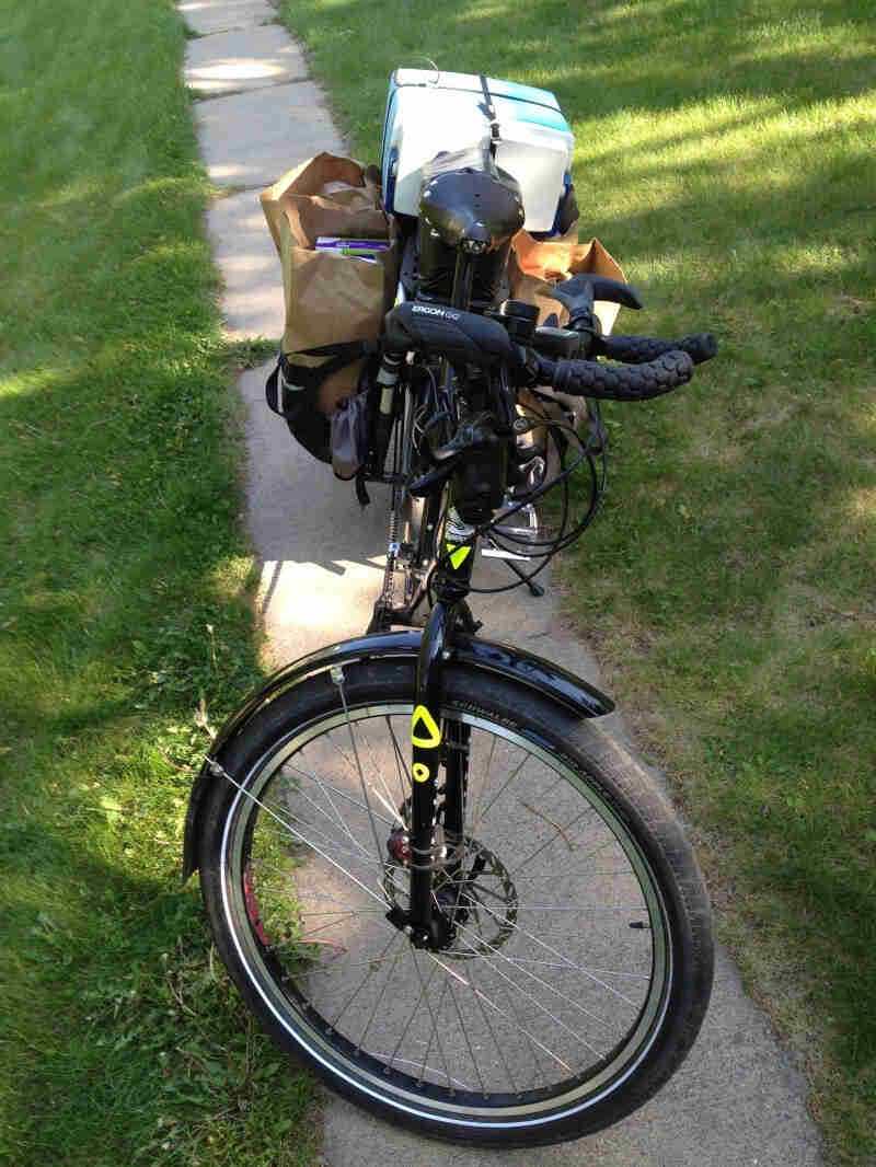 Front view of a black Surly Big Dummy bike hauling groceries, parked on a narrow sidewalk with grass on each side