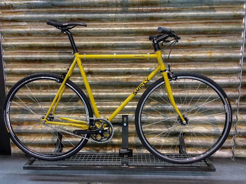 Right profile of a Surly Wednesday bike, yellow, parked in front of a steel wall