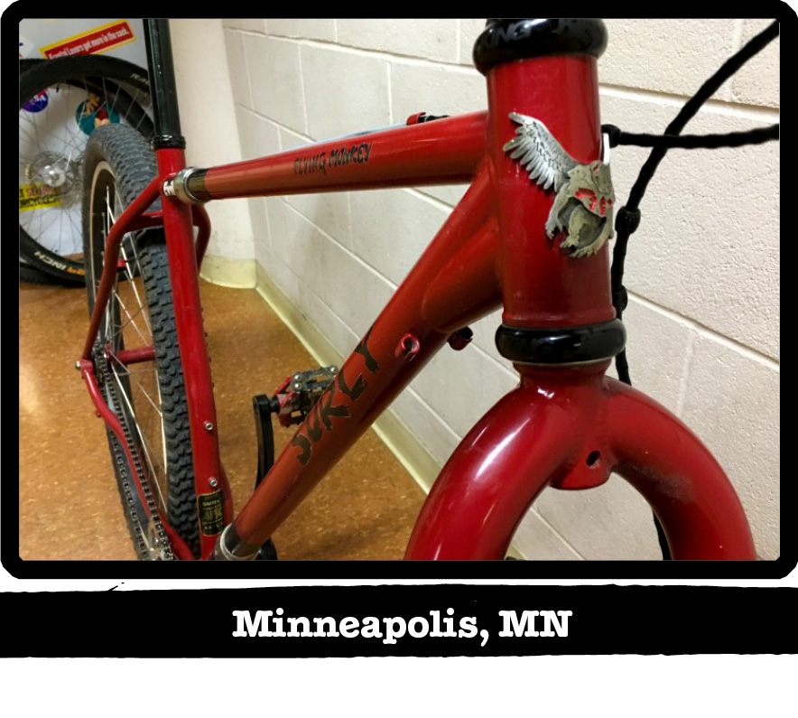 Front view of a red Surly Flying Monkey bike leaning a white cinder block wall-Minneapolis, MN banner below image