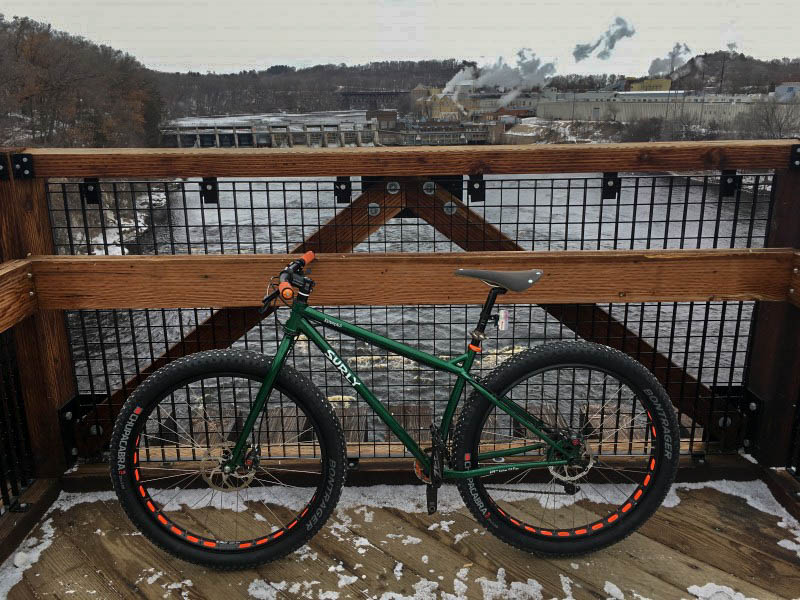 Left profile of a green Surly fat bike on a bridge over a river, with a dam in the background
