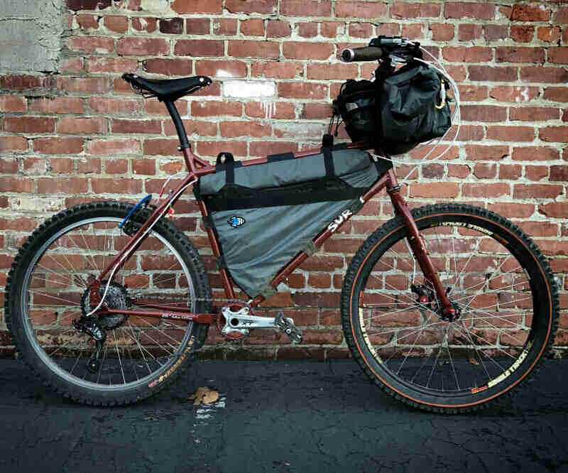 Right profile of a Surly bike, with gear, on pavement in front of a red brick wall