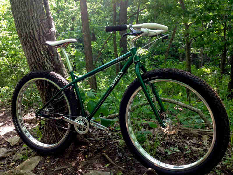 Right side view of a Surly Krampus bike, green, in a forest