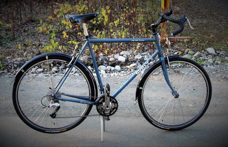 Right side view of a blue Surly Long Haul Trucker bike, parked on a gravel road