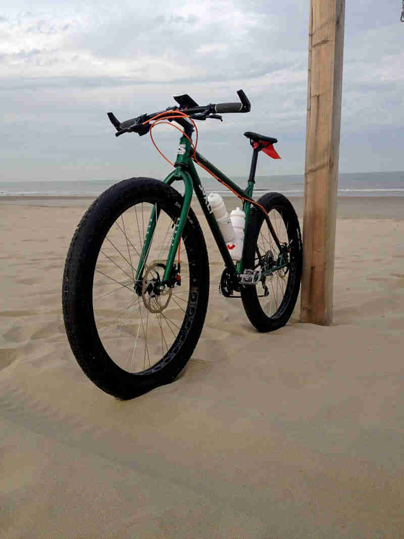 Front left side view of a Surly Krampus bike, green, on a sandy beach, with the ocean in the background