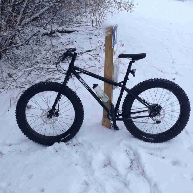 Left side view of a black Surly Ice Cream Truck fat bike, parked in the snow against a trail sign post in the woods