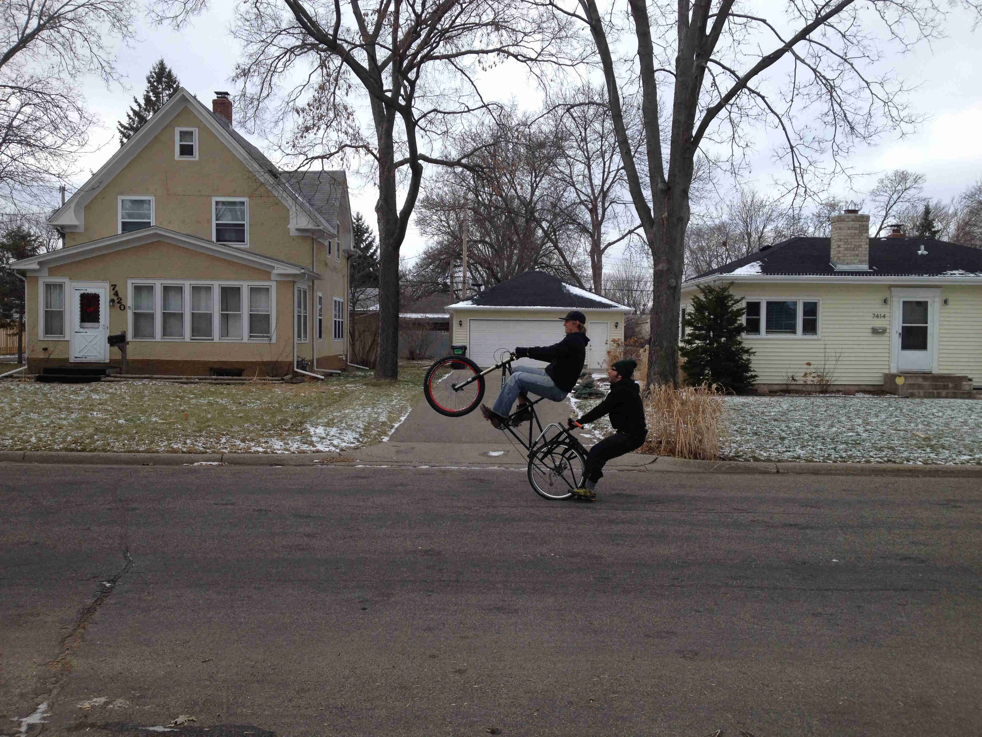 Left side view of a cyclist riding a wheelie on a black Surly Big Dummy bike with a person on back, on a paved street