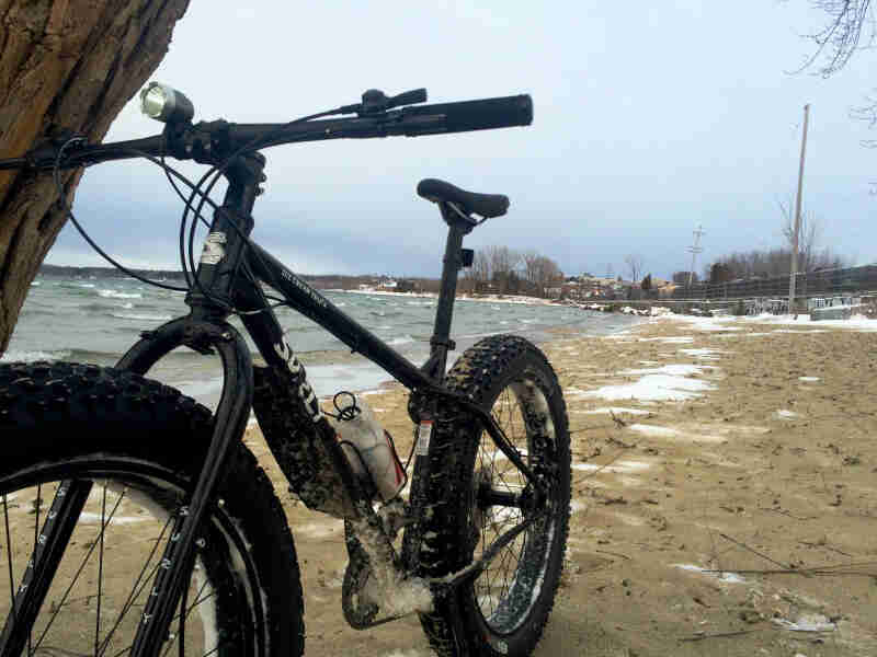 Front, left side view of a black Surly Ice Cream Truck fat bike, parked on a frozen sand lake shore