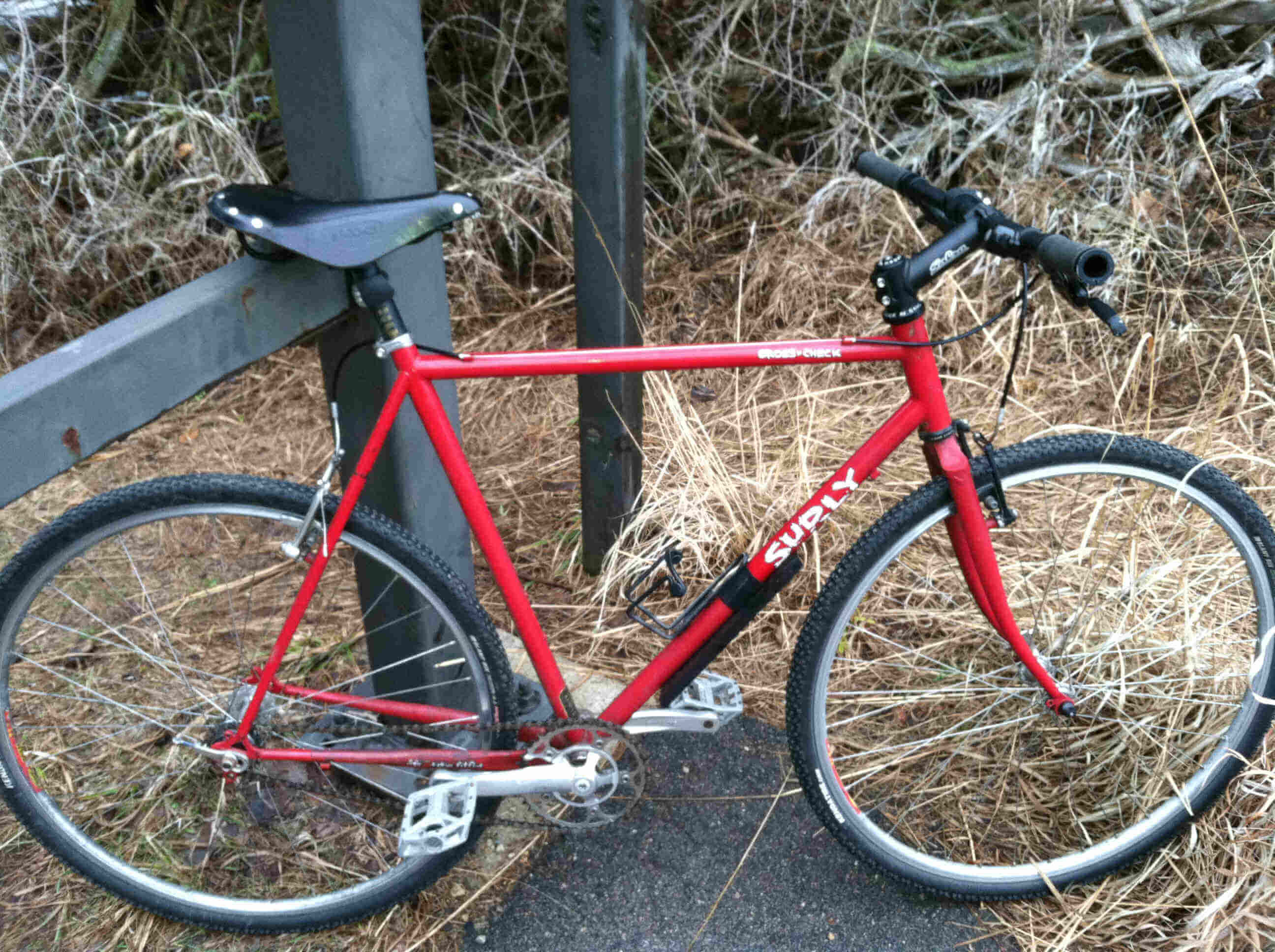 Right side view of a red Surly Cross Check bike, leaning on a steel gate post, with tall brown grass in the background