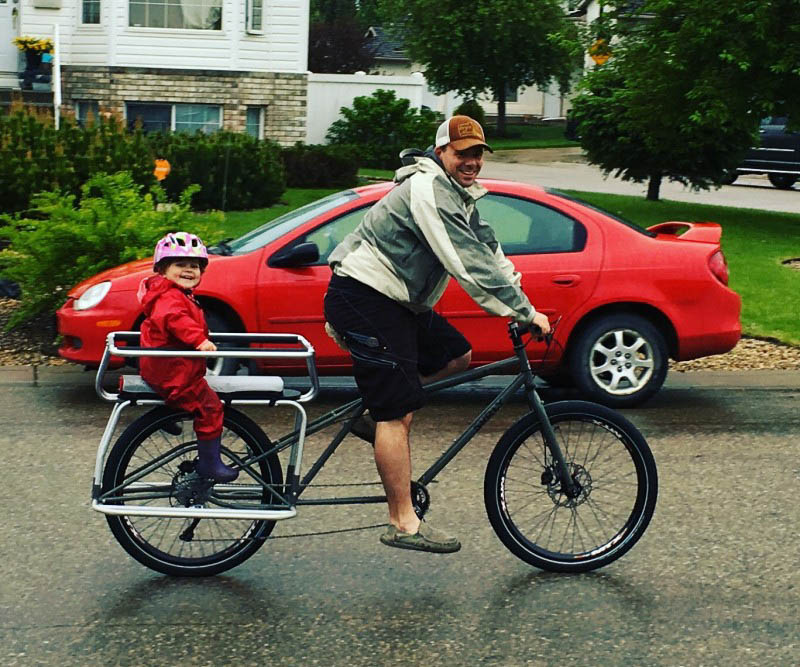 Right side view of a cyclist riding a Surly Big Dummy bike with a child in back, on a street with a car in background