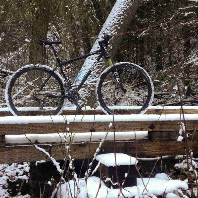 Right side view of a black Surly bike, parked on a wood crossover bridge in the snowy woods