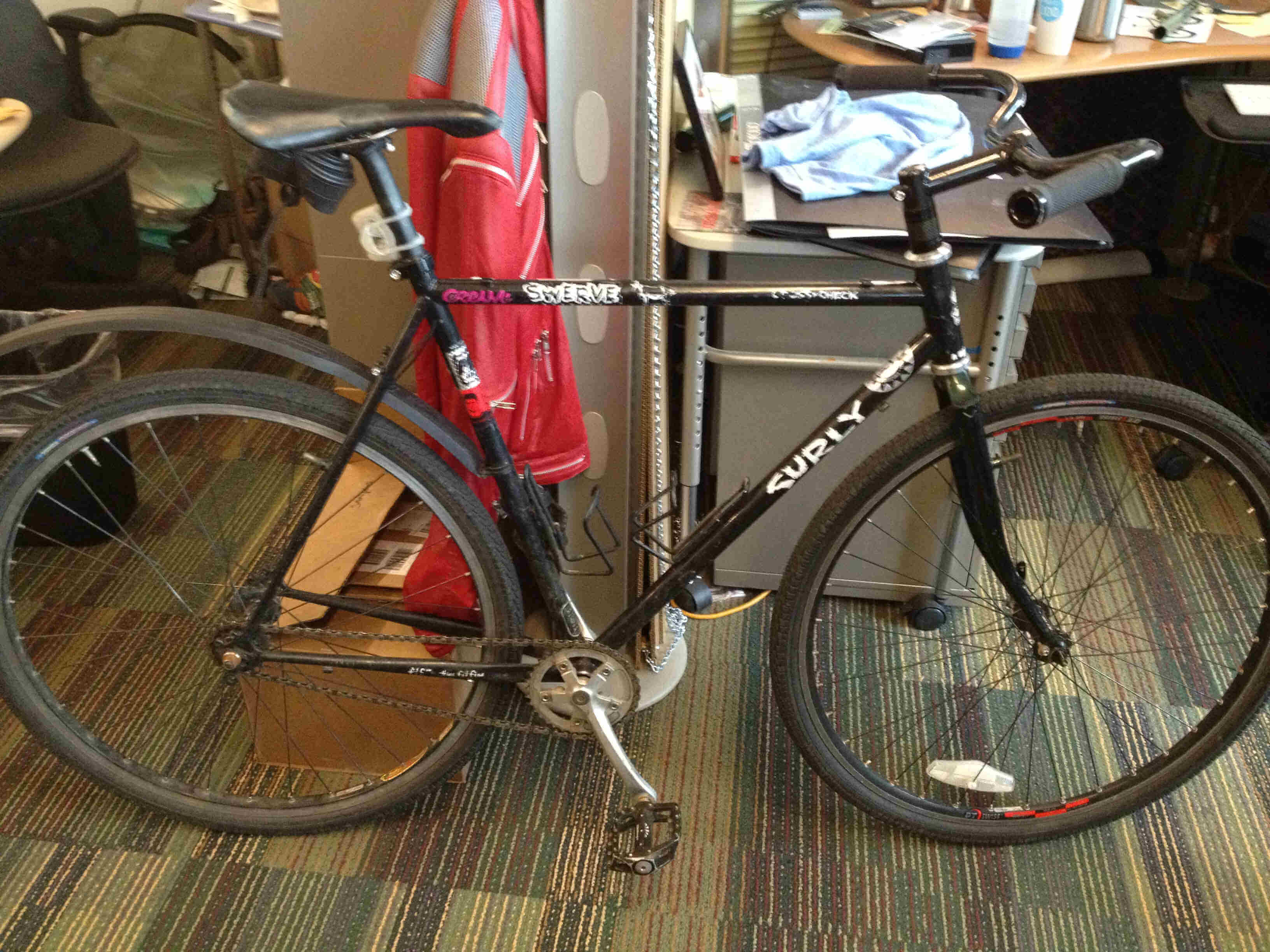 Right side view of a black Surly Cross Check bike, leaning on the end of a cubicle wall, in an office