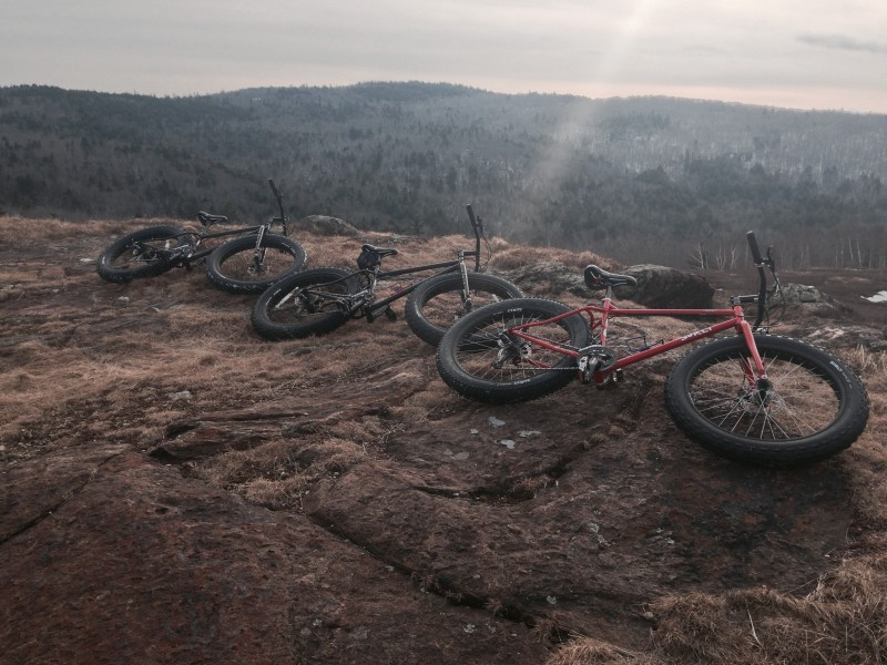 Right side view of 3 Surly fat bikes, laying on their sides at the edge of a rock cliff, with tree covered hills below