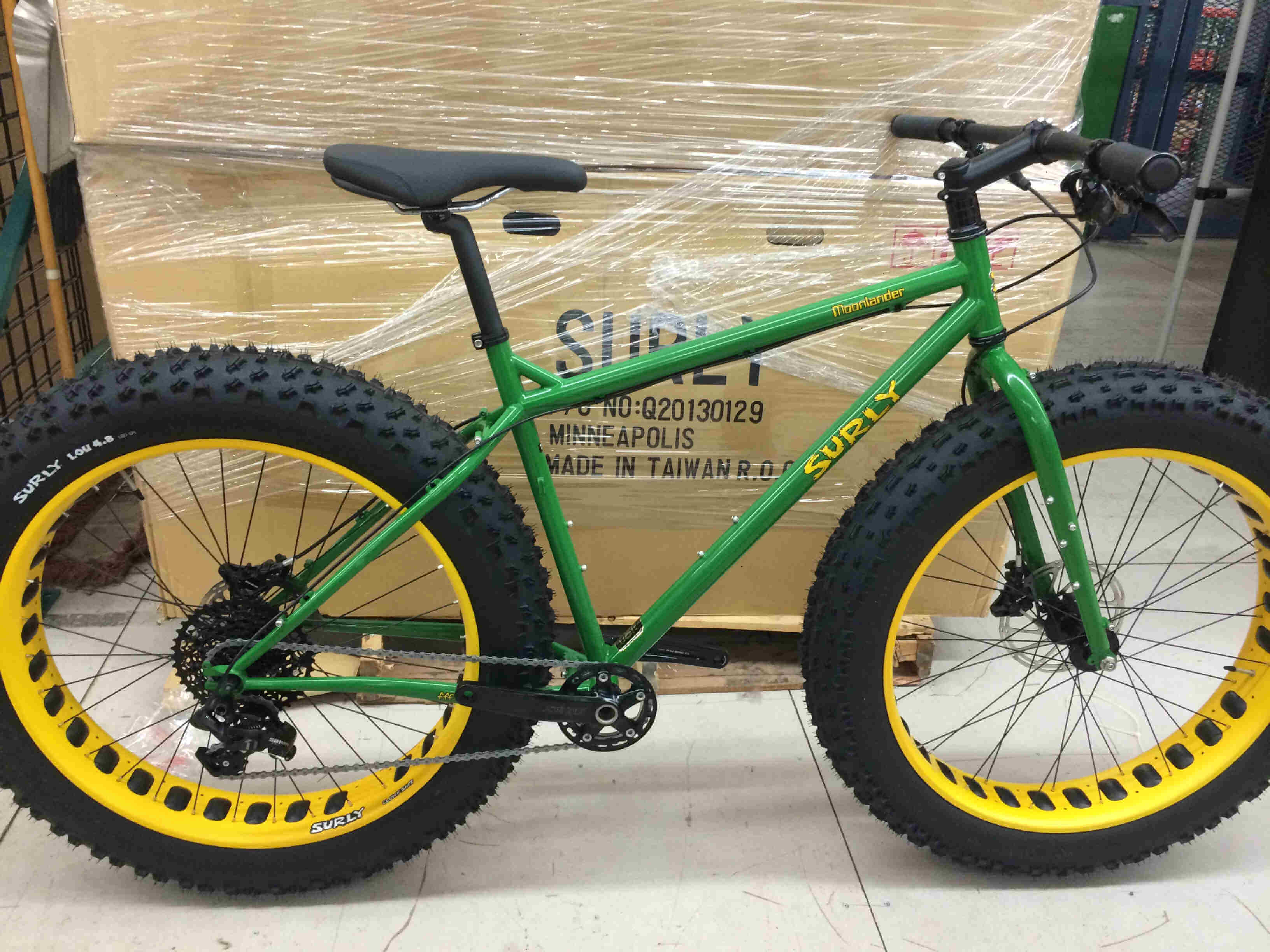 Right side view green Surly Moonlander fat bike, parked against a pallet of cardboard boxes, on a concrete floor