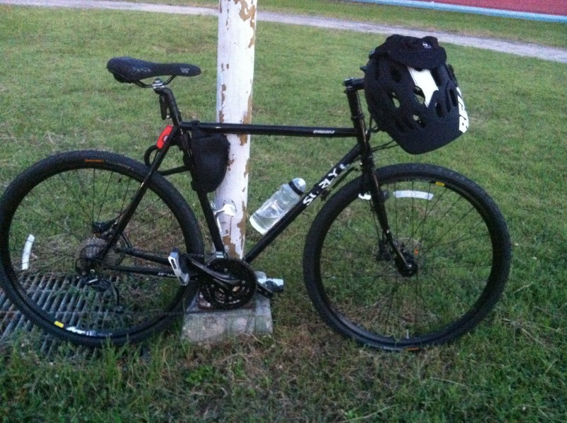 Right side view of a black Surly bike with a helmet on the handlebar, parked against a post in a grass field