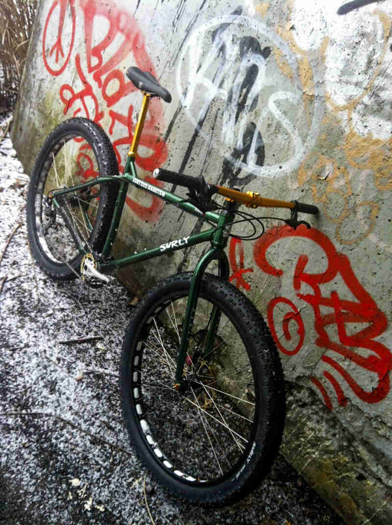 Tilted downward view of a Surly Krampus bike, green, leaning on a cement wall with graffiti