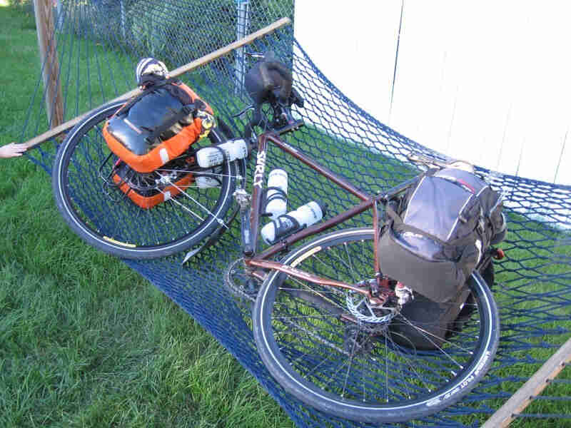 Downward, left side view of a brown Surly bike, loaded with gear and laying in a hammock, on a green grass yard