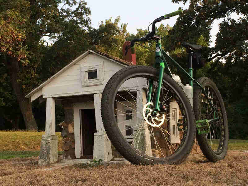 Front, ground level view of a Surly Krampus bike, green, in front of an aged log cabin, with trees in the background