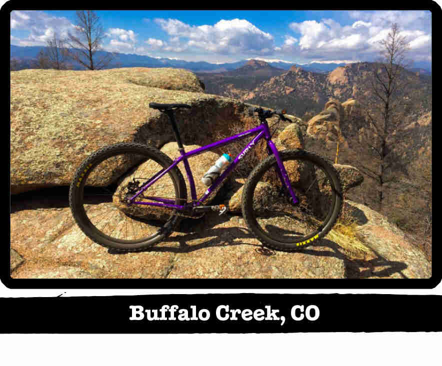 Right profile of a Surly Karate Monkey bike, purple, on a rock in the mountains - Buffalo Creek, CO tag below image