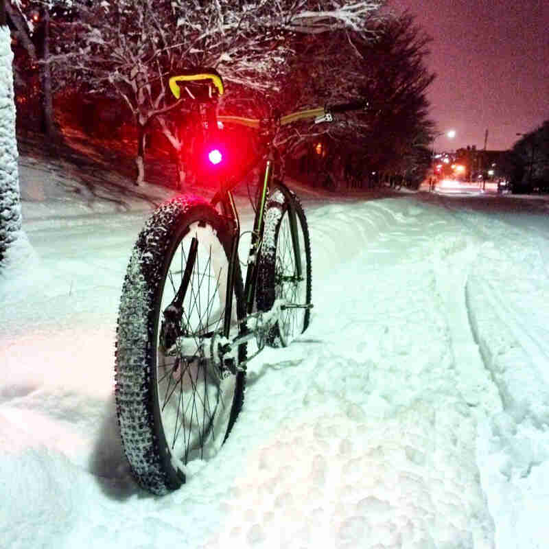 Rear view of a green Surly fat bike with a lit, red seat post light, parked in snow on the side of a street at night