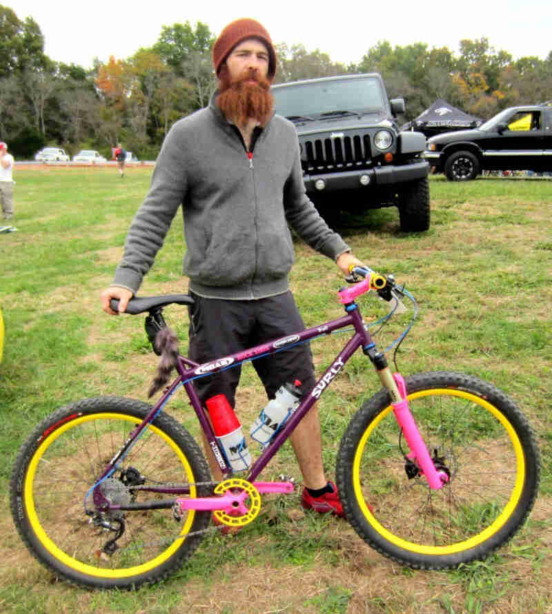 Right side view of a purple Surly Troll bike, with a cyclist standing on the left side in a grass field