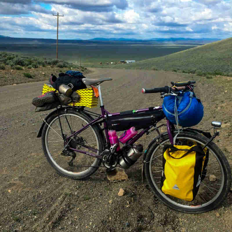 Right side view of Surly Troll bike, standing across the side of a gravel road, with vast plains in the background