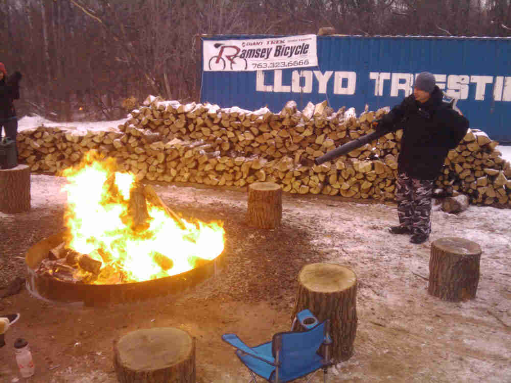 A campfire burning in snowy lot, with a person standing on the right, with a stack of split wood in the background