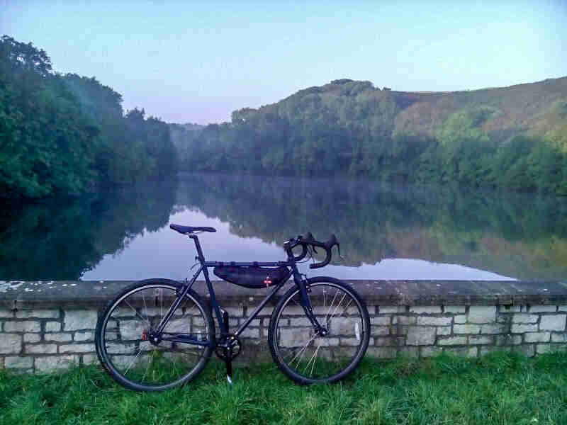 Right side view of a black Surly Cross Check bike, park in grass against a stone wall, in front of a pond