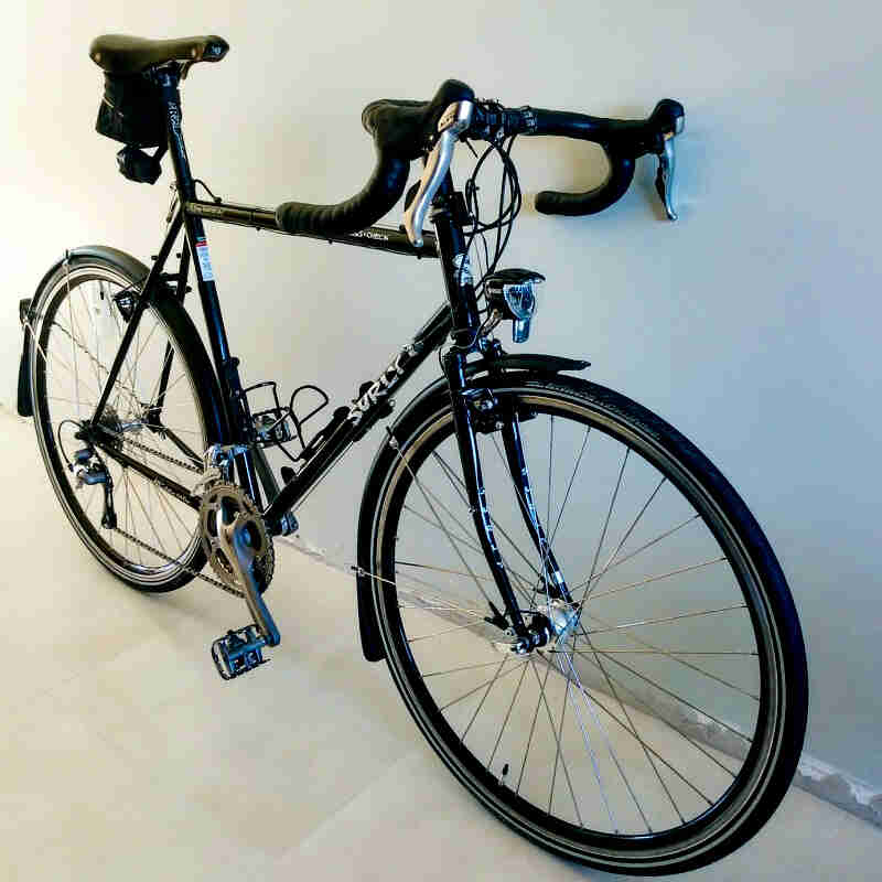 Right side angled view of a Surly Cross Check bike, black, leaning against a white wall
