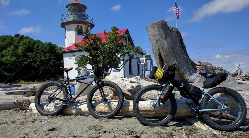 Side view of 2 Surly bikes facing each other, parked in sand with logs, with a lighthouse building in the background