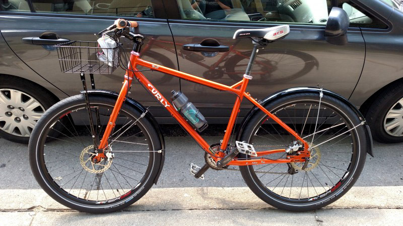Left profile of an orange Surly Troll bike on a sidewalk, with a car on the street in the background