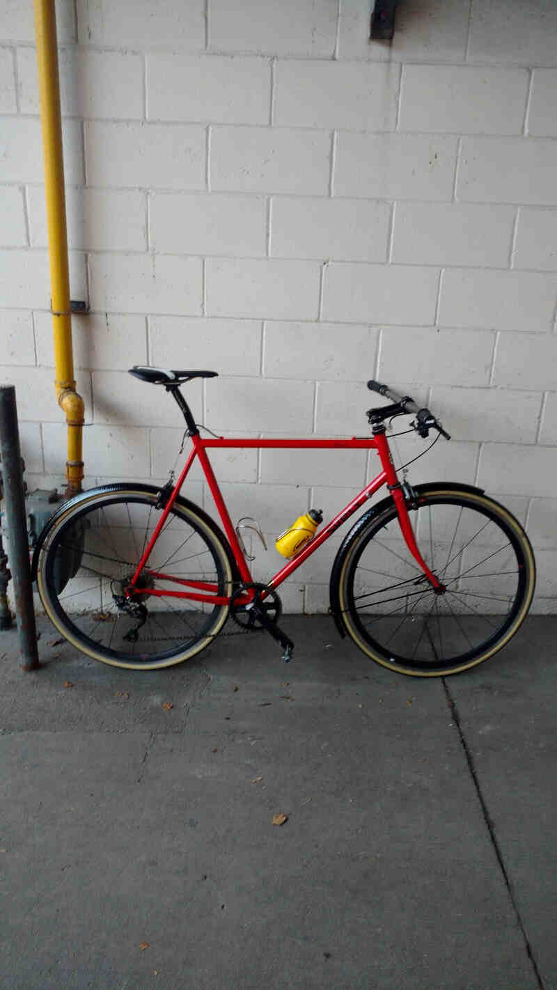 Ride side view of a Surly Pacer bike, red, on a sidewalk leaning on a white cinder block wall