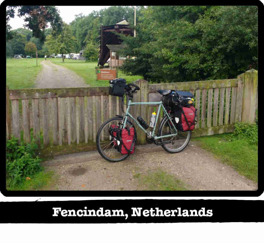 Left profile of a Surly Long Haul Trucker bike, mint, leaning on a wood gate - Fencindam, Netherlands tag below image