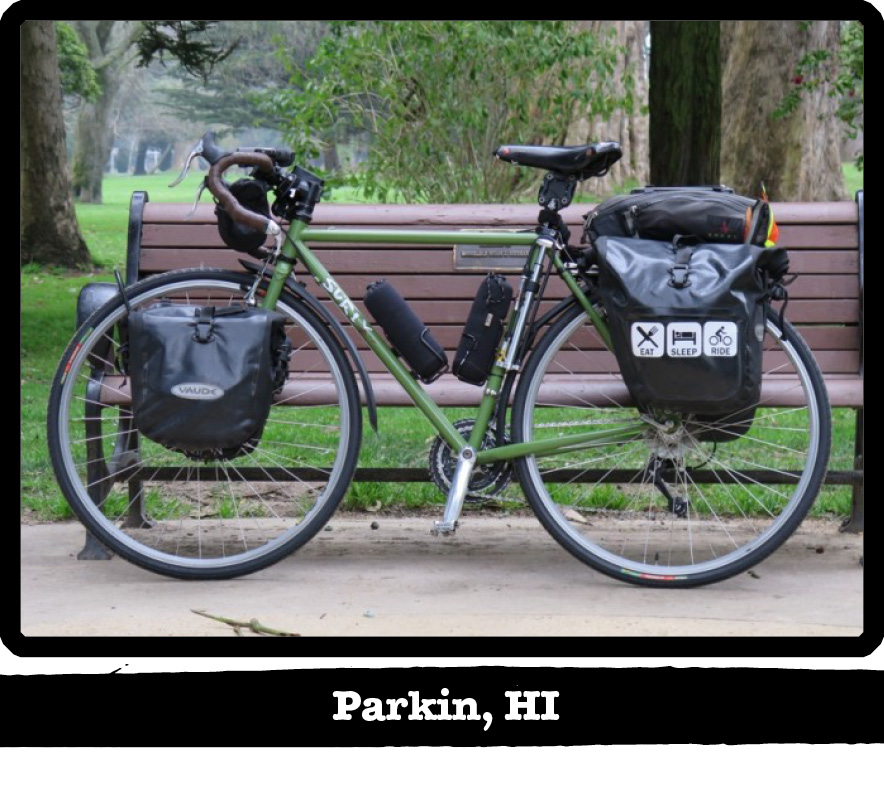 Left profile of a green Surly bike with gear, leaning on a park bench with trees behind-Parkin, HI banner under image