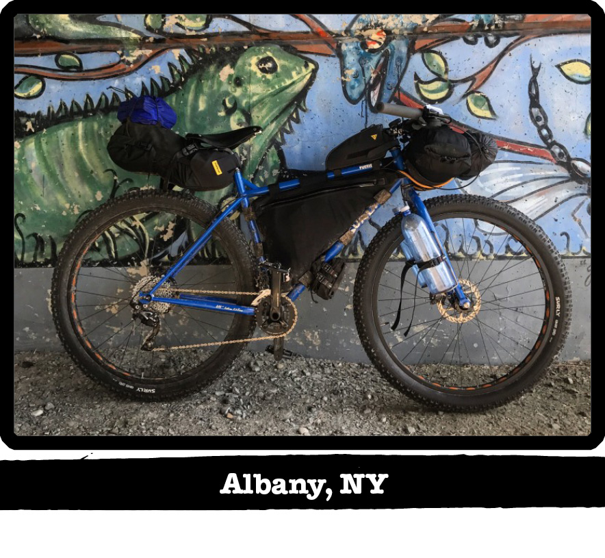 Right profile view of a blue Surly bike with gear leaning on wall with a painting-Albany, NY banner under image