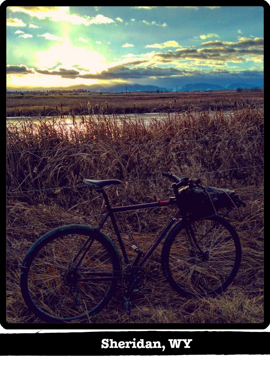 Right profile view of a Surly bike leaning on a barbed wire fence wetlands and sun shining through cloud behind-Sheridan,WY banner below image